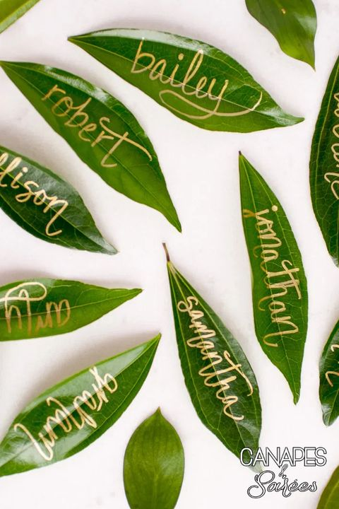 leaf place cards with names written in gold lettering
