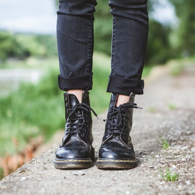 woman standing in park with leather boots