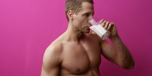 Young man with naked torso is drinking a glass of milk, portrait