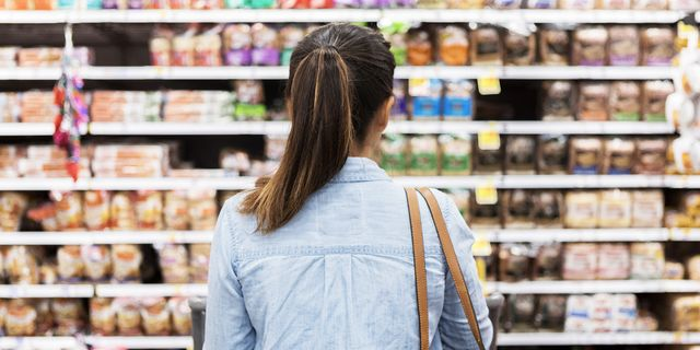 woman standing in front of bread aisle in grocery store
