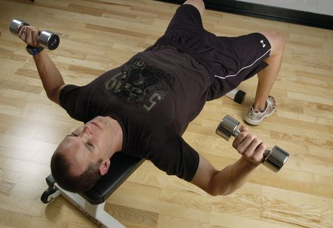 (GA) ---FE17FTWEIGHTS-- Lee Cherry, exercise physiologist with Strength from Within LLC demonstrates proper dumbell press form by keeping his feet flat on the ground and back and arms straight. Glenn Asakawa / The Denver Post