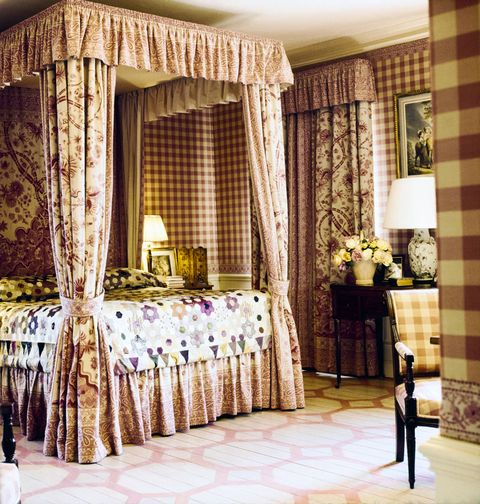 vogue, july 01, 1971   lee radziwills bedroom in the country home she shares with prince stanislaw and their two children, turville grange, buckinghamshire, england the room features a canopy bed made of pink floral and paisley linen toile, a silk taffeta patchwork quilt covering the bed, silk taffeta squares covering the walls, and a pink and white stenciled wood floor the same pink check that covers the walls covers a side chair, and a table stands against a wall with a lamp and a vase of flowers on it on the bedside table there is a lamp, a framed print, and some books horst p horstconde nast via getty images