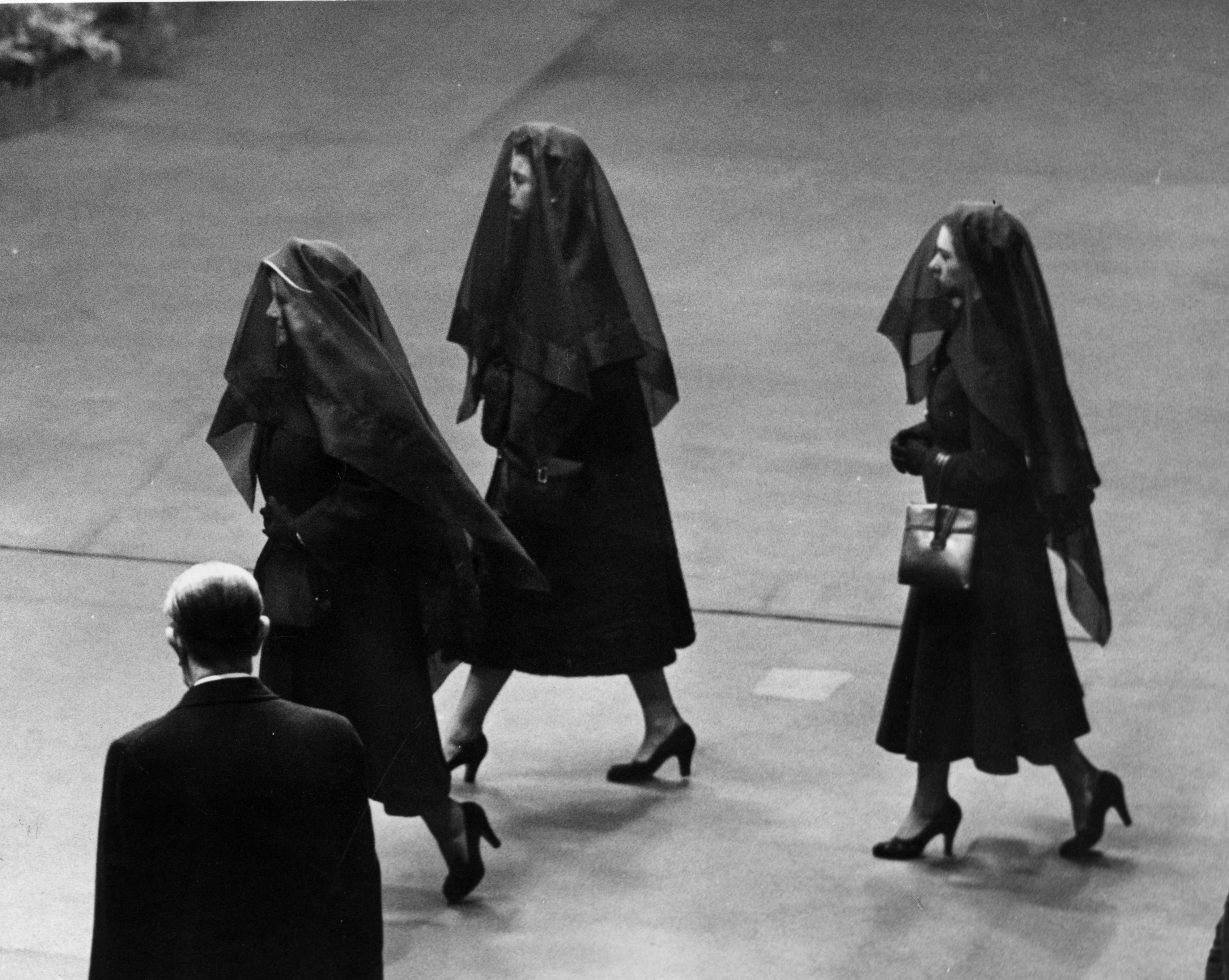 Queen Elizabeth the Queen Mother, Queen Elizabeth II, and Princess Margaret wearing veils on their way to the funeral of King George VI.