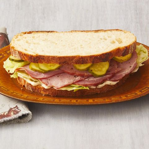 ham sandwich with quick pickles on brown plate