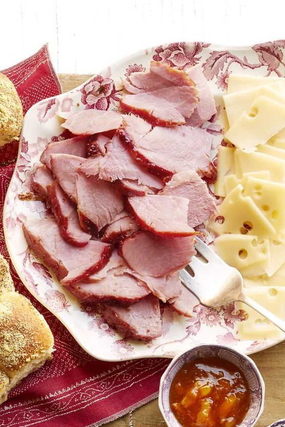 honey glazed ham and checkerboard rolls on platter with cheese slices and bowls of jam