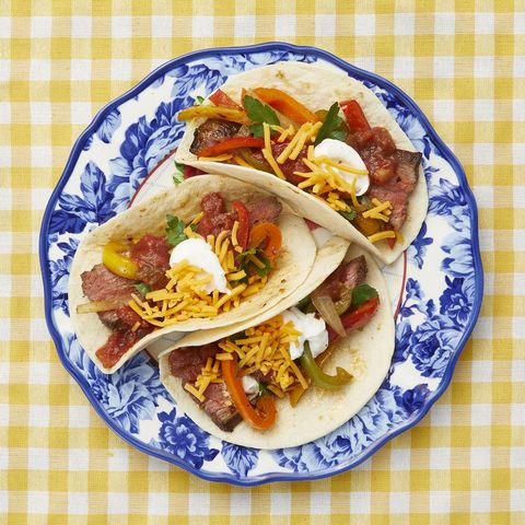 beef fajitas on blue plate and yellow background