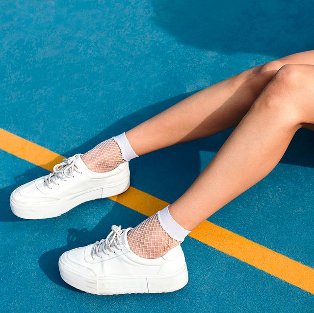 woman sitting on blue and yellow tennis court wearing white sneakers leg makeup self tanner leopard print skirt