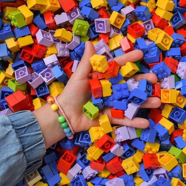 kid's hand holding legos