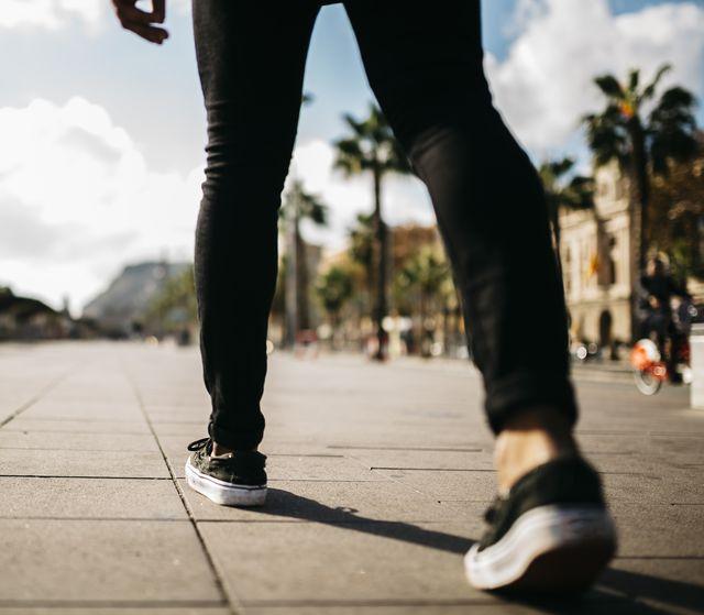 legs of a man walking on pavement