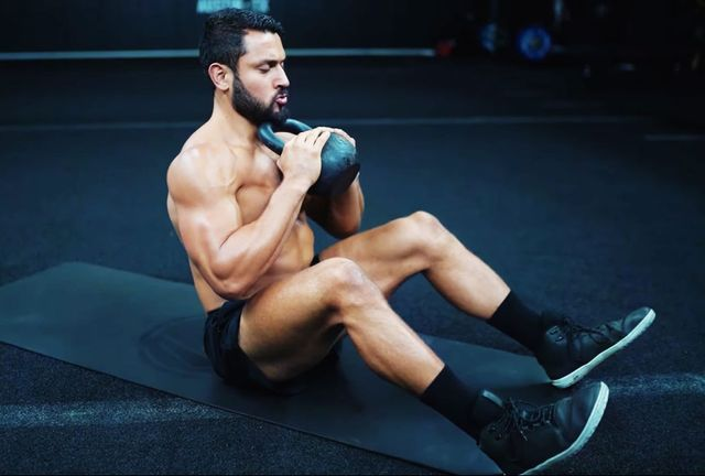 man doing crunches with a kettlebell