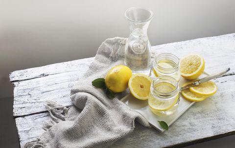 Lemon water on white wooden table. Still life.