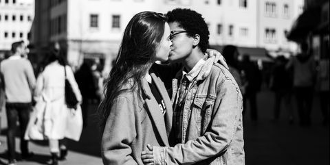 lesbians kissing while standing on city street