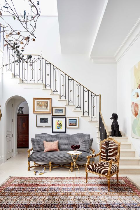 the familys french poodle hugo greets guests in the double height foyer and framed works by canadian artists hang over a velvet settee