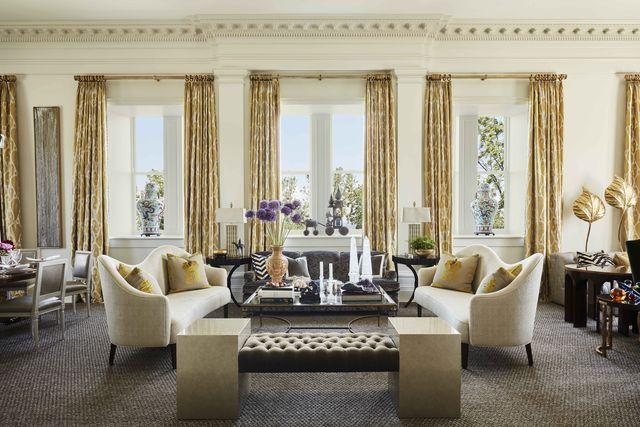 in the living room silk ikat draperies frame lofty windows beneath corinthian crown molding