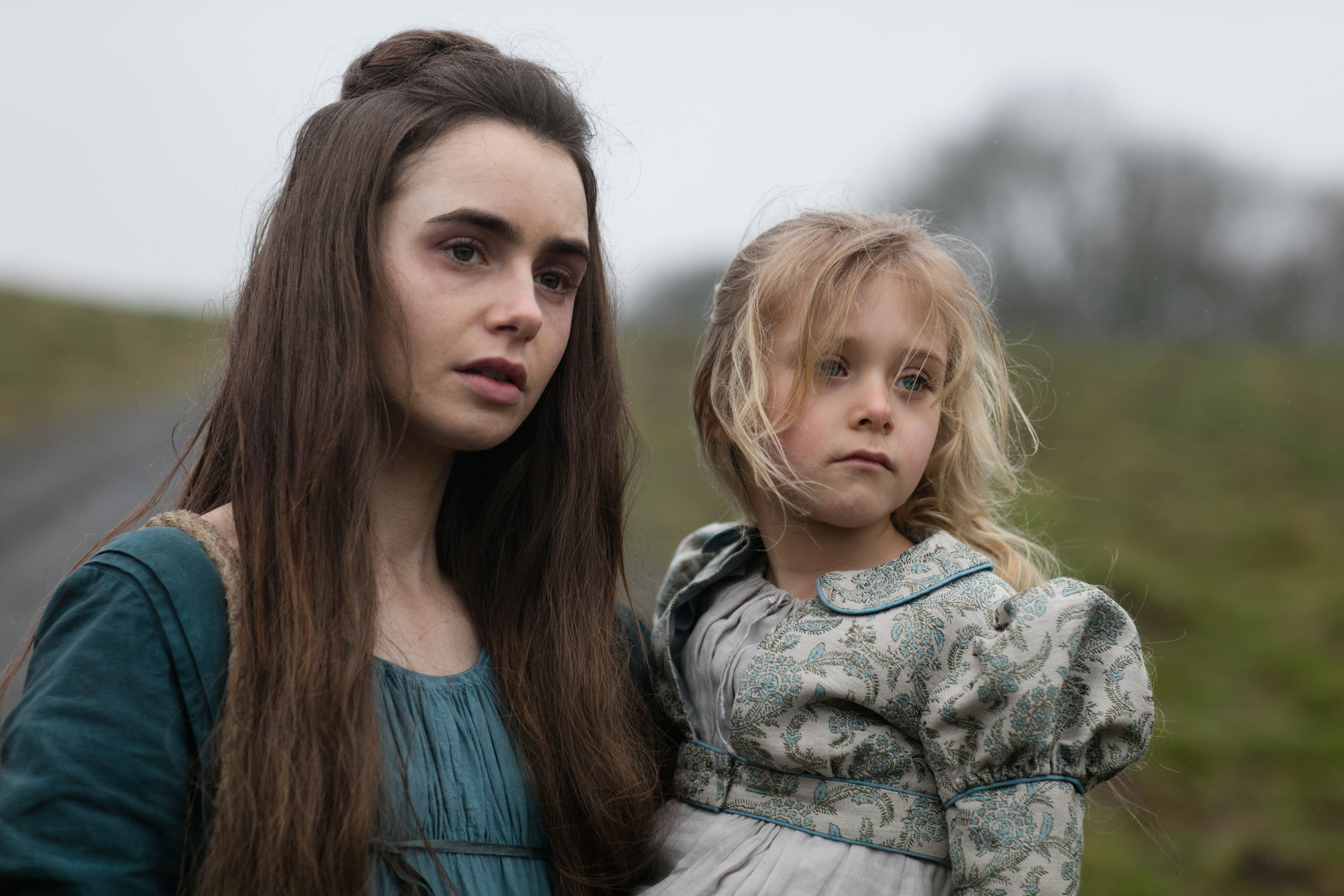 Lily Collins as Fantine in Les Misérables, holding her daughter Cosette.