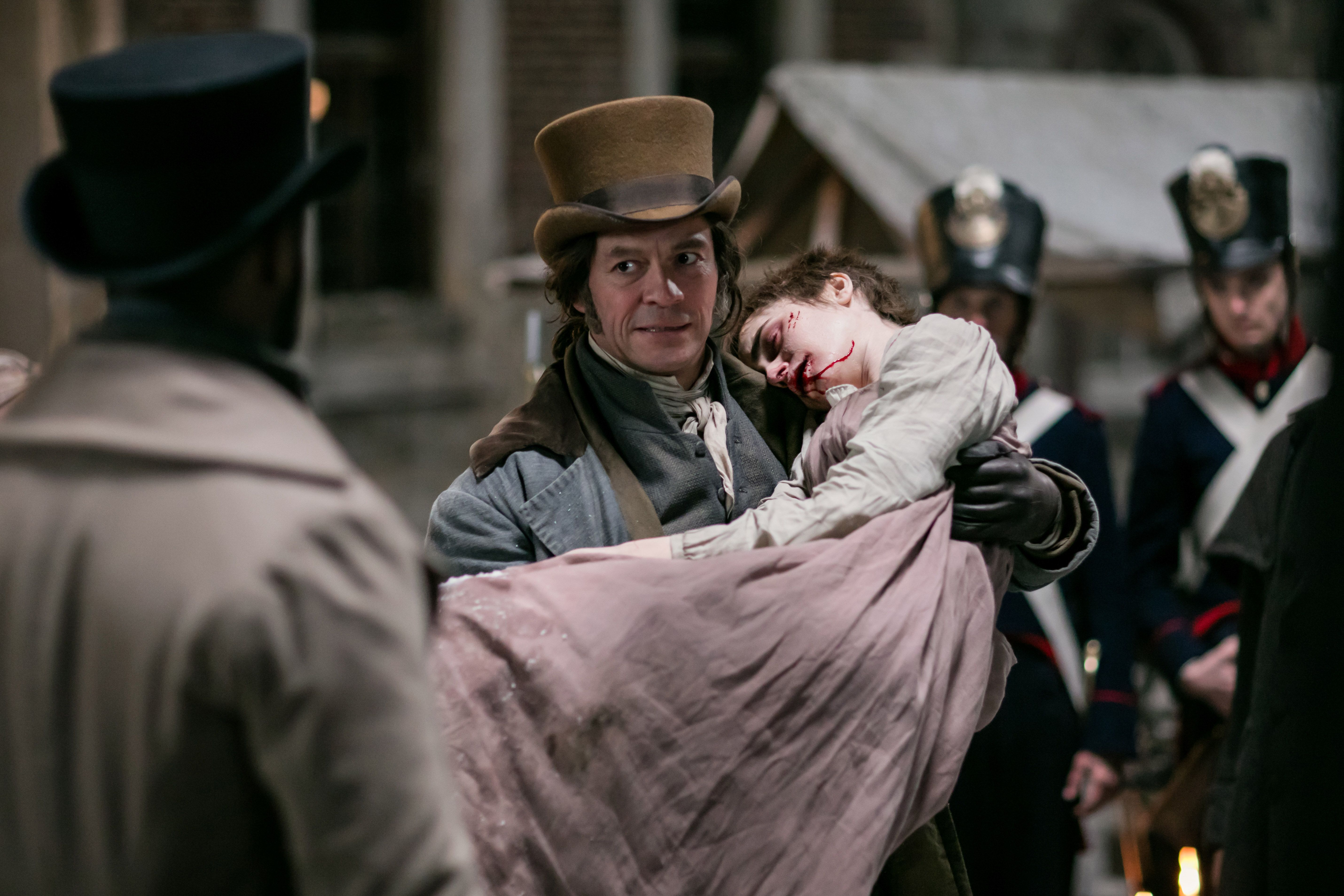 Dominic West as Jean Valjean and Lily Collins as Fantine in Les Misérables.