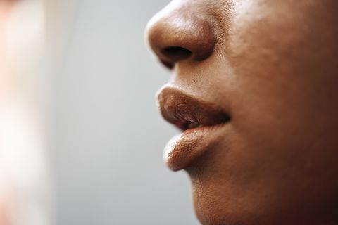 nose, lips and cheek of young woman, close up
