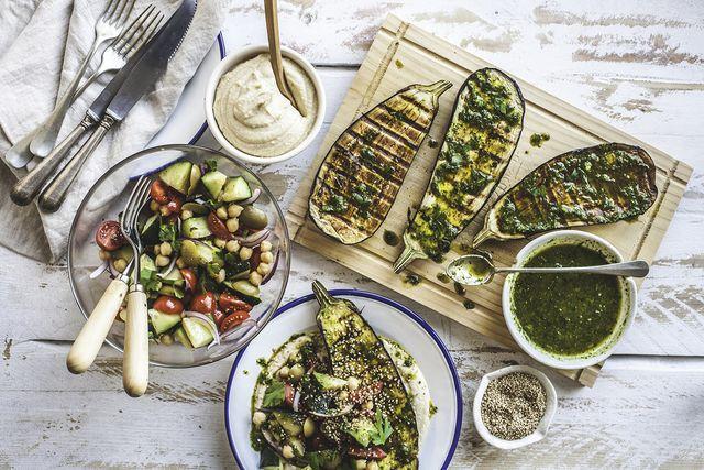 tafel vol gegrilde groenten, salade, aubergine, kruidensaus