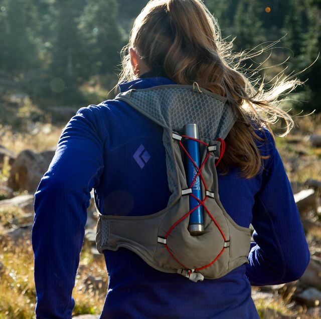 woman running on mountain with lifestraw