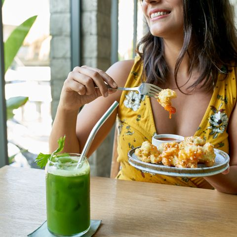 lifestyle portrait of smiling healthy ethnic woman eating an organic plant based cauliflower meal for vegetarians and drinking green smoothie