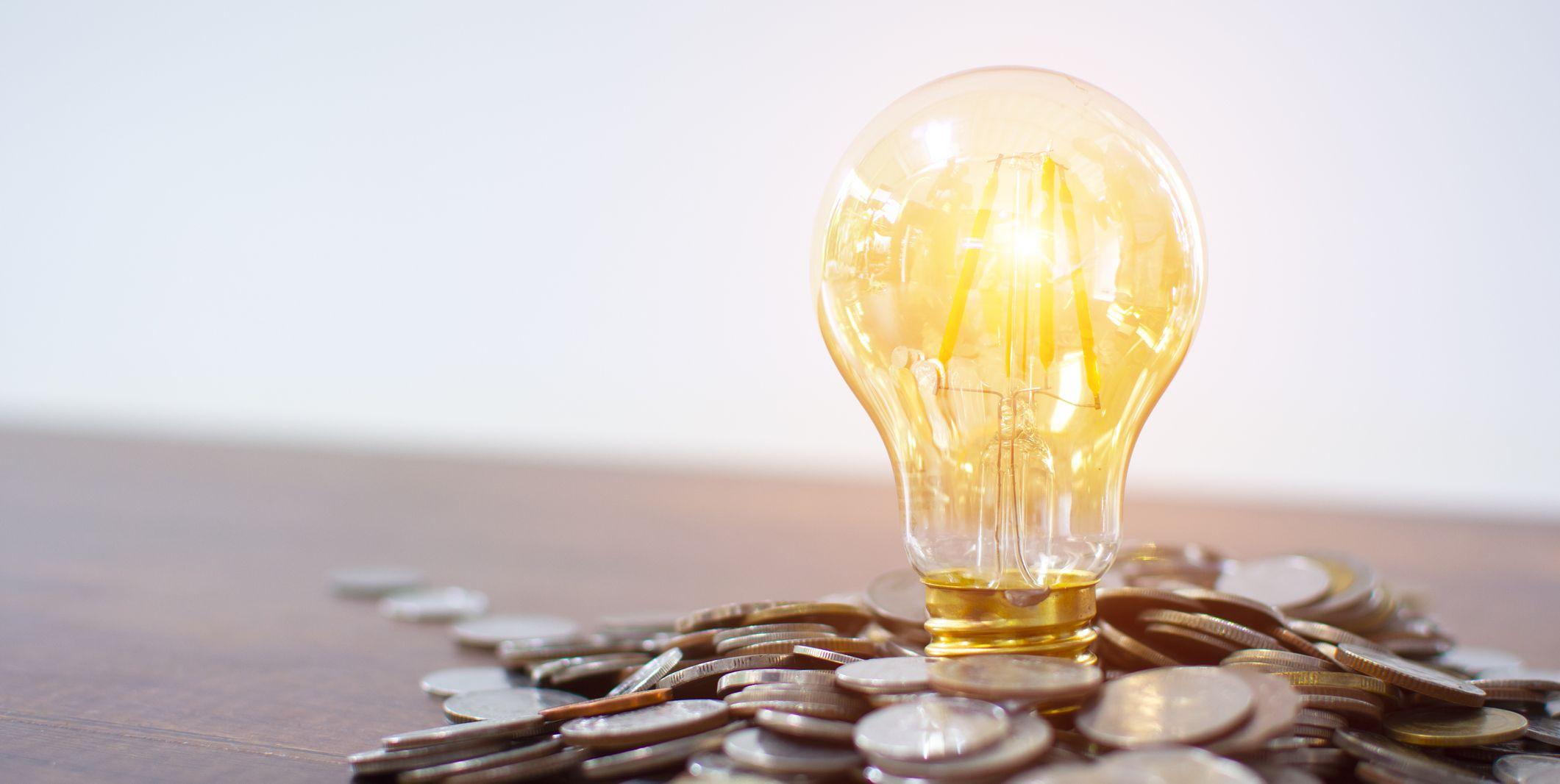 Light bulb on apile of coins