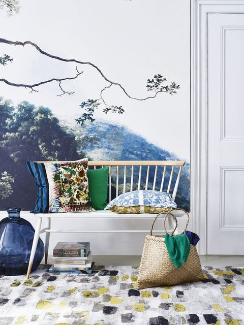 hand painted mural tree landscape in a hallway white chair with colourfull cushions on