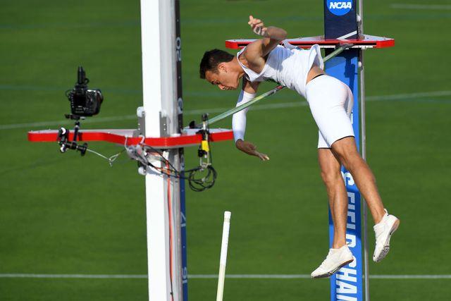 el pertiguista estadounidense kc lightfoot salta por encima del listón con salto con pértiga en una competición de la ncaa