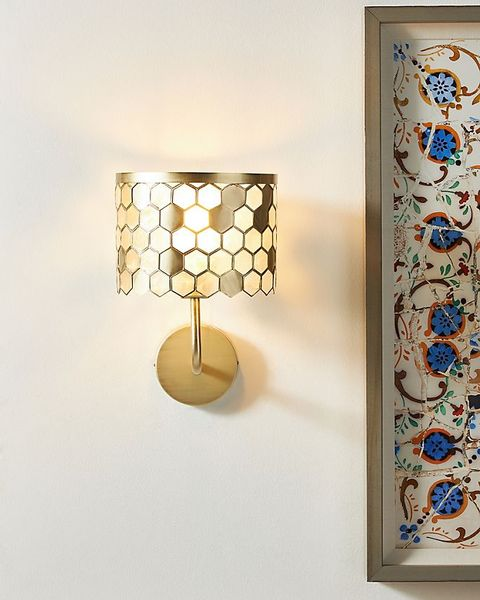 honeycomb sconce attached to wall next to painting
