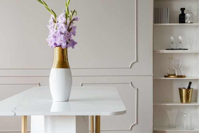 lavender purple flowers in a golden vase on a white marble table in an elegant dining room interior with molding on beige walls