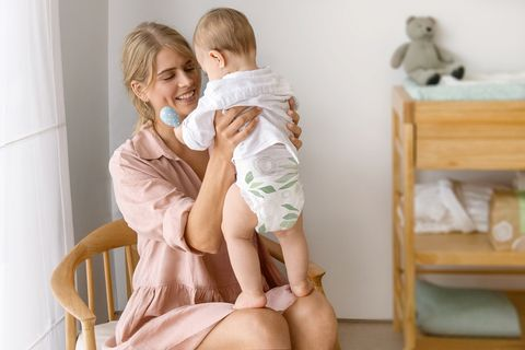 una madre sostiene a su bebé con pañales lillydoo green