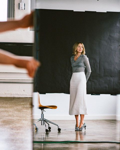 lisa stands in a room wearing zebra print heels, a white midi skirt, and a ribbed gray collared shirt