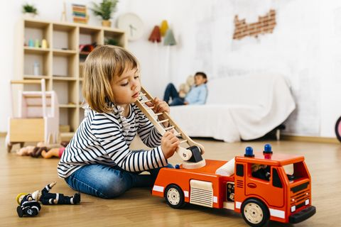 little blond playing with a wooden fire truck