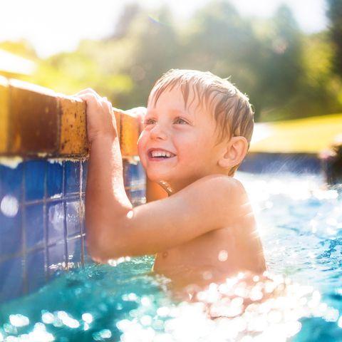 Little boy having fun in the swimming pool in summertime
