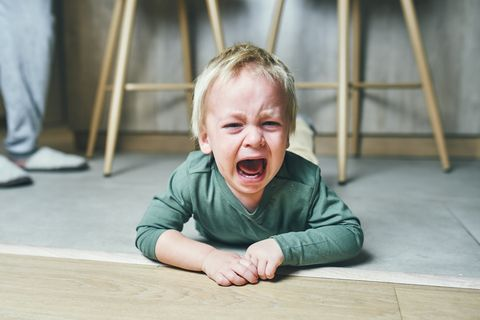a little boy with blond hair, two years old, is lying on the floor and crying hysterically after kindergarten at home parenting