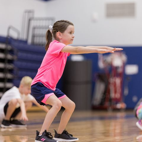 little girl doing squats in pe class