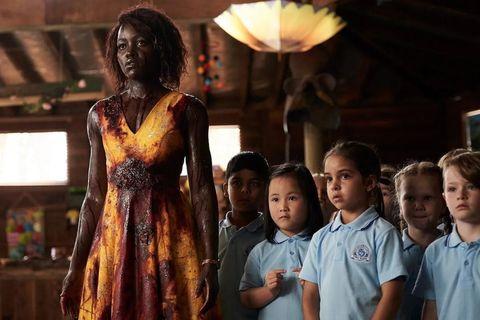 lupita nyong'o cubierta de sangre frente a unos niños en little monster