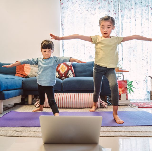 little sibling enjoy online yoga class with laptop computer at home