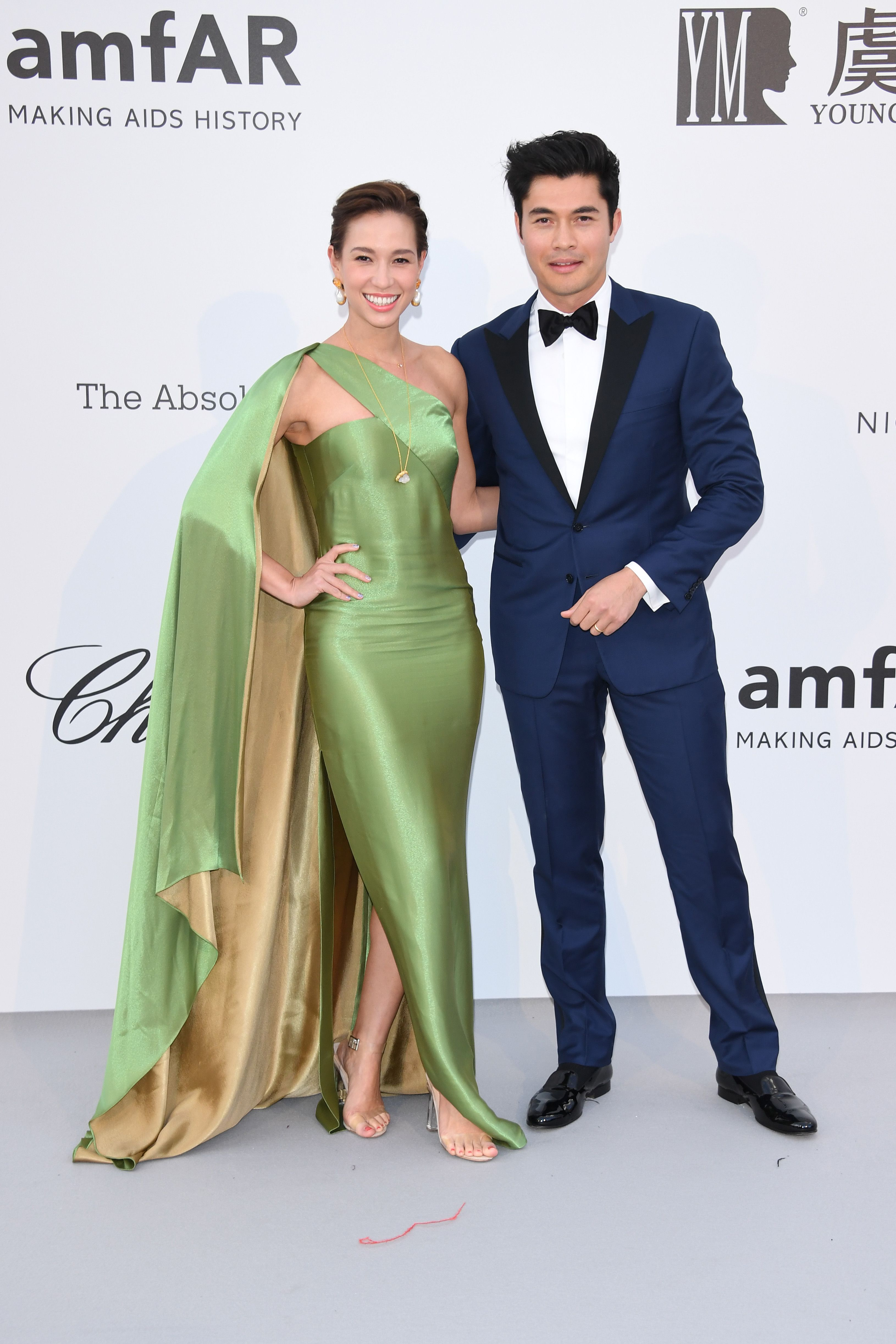 Liv Lo and Henry Golding Lo in a green and tan cape dress by Ralph Lauren Collection and Golding in a Ralph Lauren Purple Label suit.