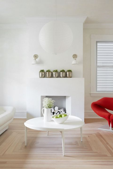white living room with paper pendant light and red chaire