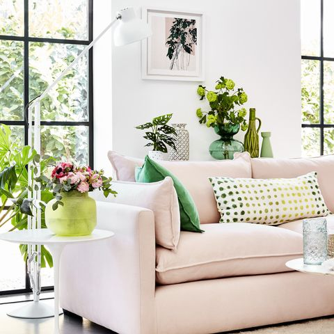 pink sofa in a white room  with green plants around and green patterned cushions