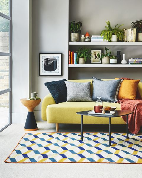 sitting room, yellow sofa white shelf behind with a blue and yellow patterned rug on the floor