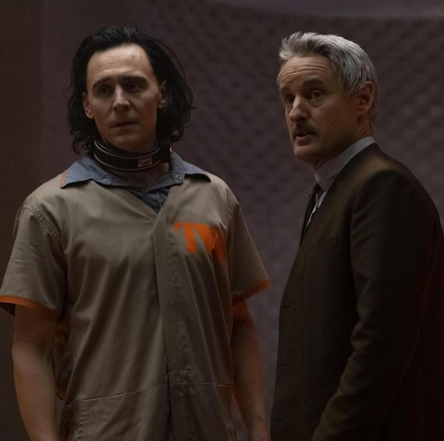 tom hiddleston as loki and owen wilson as mobius in loki, hiddleston wears a beige prison jumpsuit with tva logo