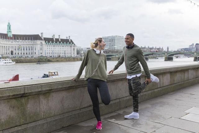 uk, london, two happy runners stretching at riverwalk
