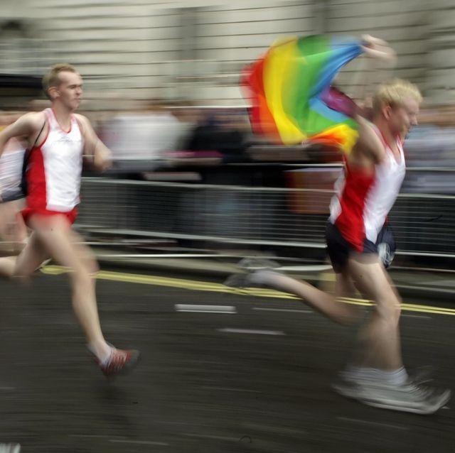 men holding the rainbow flag run during