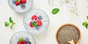 Long banner with chia pudding, top view, fresh berries raspberries, blueberries. Three glass, light wooden background, flowers.