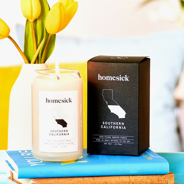 homesick candles sitting on stack of books in bright living room with yellow tulips and teal decor