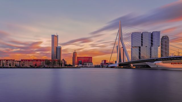 long exposure of rotterdam skylines at sunset with new meuse river on froreground, netherlands