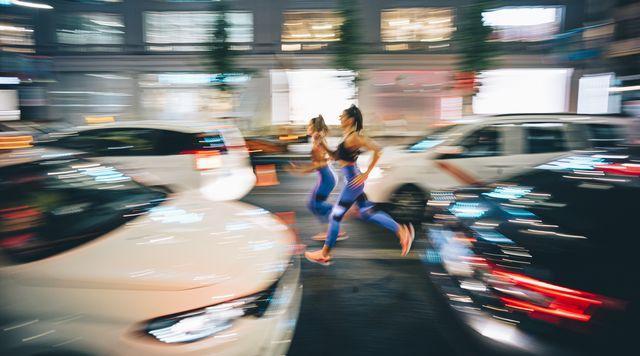 dos mujeres corren entre los coches por la calle de una ciudad