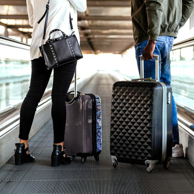 people on moving beltway in airport with luggage
