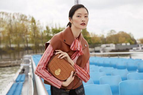 台灣女模李晨華手拿Longchamp駝色壓紋馬鞍包,完美示範法國女人的時髦感。